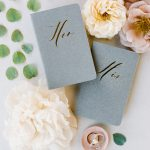 Personalized his and hers grey vow books and rings from Elegant Fusion Wedding