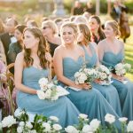 bridesmaids in blue dresses and small bouquets seated during the ceremony for elegant fusion wedding