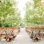 wedding ceremony lined with sycamore trees and beautiful fall floral arrangements on the aisle.