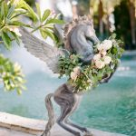wedding flowers decorating pegasus statuefrom Elegant Fusion Wedding