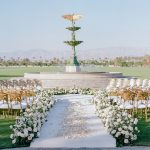 White floral aisle with petals and gold chameleon chairs at the in-the-round ceremony for elegant fusion wedding