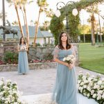 bridesmaids in blue dresses and small bouquets walk the floral aisle ceremony for elegant fusion wedding