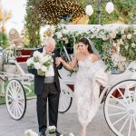 The bride with her father and horse and carriage at the ceremony at Empire Polo Club elegant fusion wedding