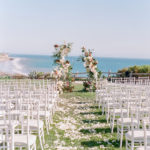 The seaside ceremony was kept simple to celebrate the amazing coast line. Clear plexiglass panels served as the backdrop and were decorated with amazing textural floral and greenery including magnolia leaf, orchids, hydrangea anthurium, smilax and roses.