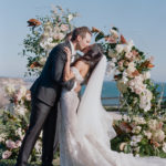 The first kiss as husband and wife in front of a dramatic scene: an abundant floral display and the gorgeous Pacific Ocean.
