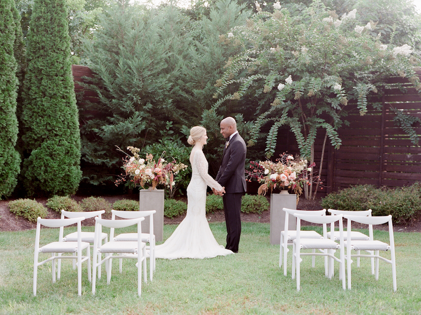 An intimate backyard wedding with a bride and groom holding hands in Nashville