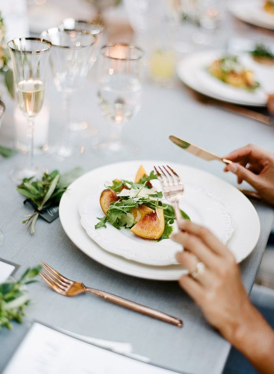 A plated wedding dinner with peaches and arugula.