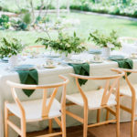 A long rectangular table is set outside with green and white details to blend with the backyard at this baby shower.