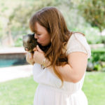 A guest holds and kisses a piglet at a baby shower petting zoo.