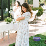 A guest holds a white bunny at a baby shower petting zoo.