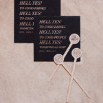 """Custom wedding cocktail napkins printed with the couple's """"hell yes"""" wedding theme are styled with wooden stir sticks decorated with a bulldog and a bullseye to honor the couple's dog."""