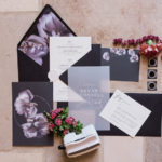 a black and white wedding invitation suite with vellum details is styled with pink and red floral.