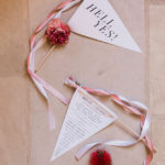 "A ceremony program is fashioned into a pennant with a bell and ribbon streamers with the wedding's ""hell yes"" motto on the front"