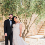A bride and groom pose in front of an olive tree outside of Sunstone Winery for their wine country destination wedding.