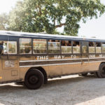 "Guests arrive to this destination wedding in wine country on a vintage school bus painted black with the wedding's motto: ""This way to our hell yes wedding"""