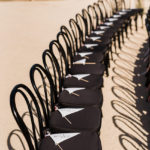 Ceremony programs fashioned into pennants with bells and ribbon streamers rest on black ceremony chairs.