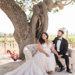 A bride and groom sit on a love seat at their ceremony to fully take in the officiant's words.