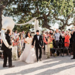 Newlyweds walk down the aisle accompanied by a brass band at this destination wedding in wine country.