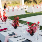 a dinner table is decorated with crisp white linen, black chairs and flatware and bright multi-colored napkins and flower centerpieces.