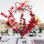 A modern centerpiece with red flowers sits on a crisp white table at this destionatin wedding in California wine country.