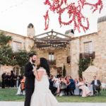 The bride and groom have their first dance under a colorful floral installation at this outdoor destination wedding.