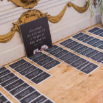 "Escort cards are displayed on a table with the sign ""welcome to a moment 12 years in the making at this destination wedding."